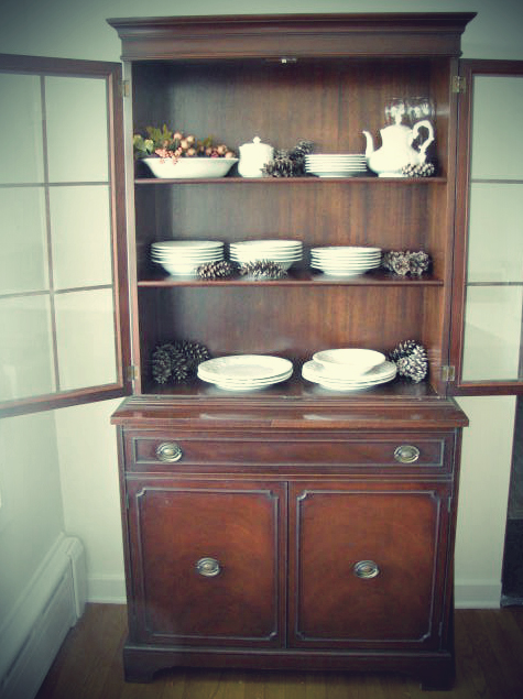 winter interior decorating: china hutch with stoneware, pine cones, gooseberries