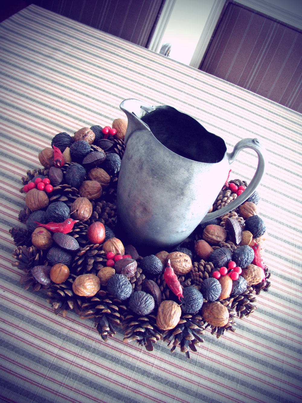 winter interior decorating: pewter jug with pine cone and nut wreath